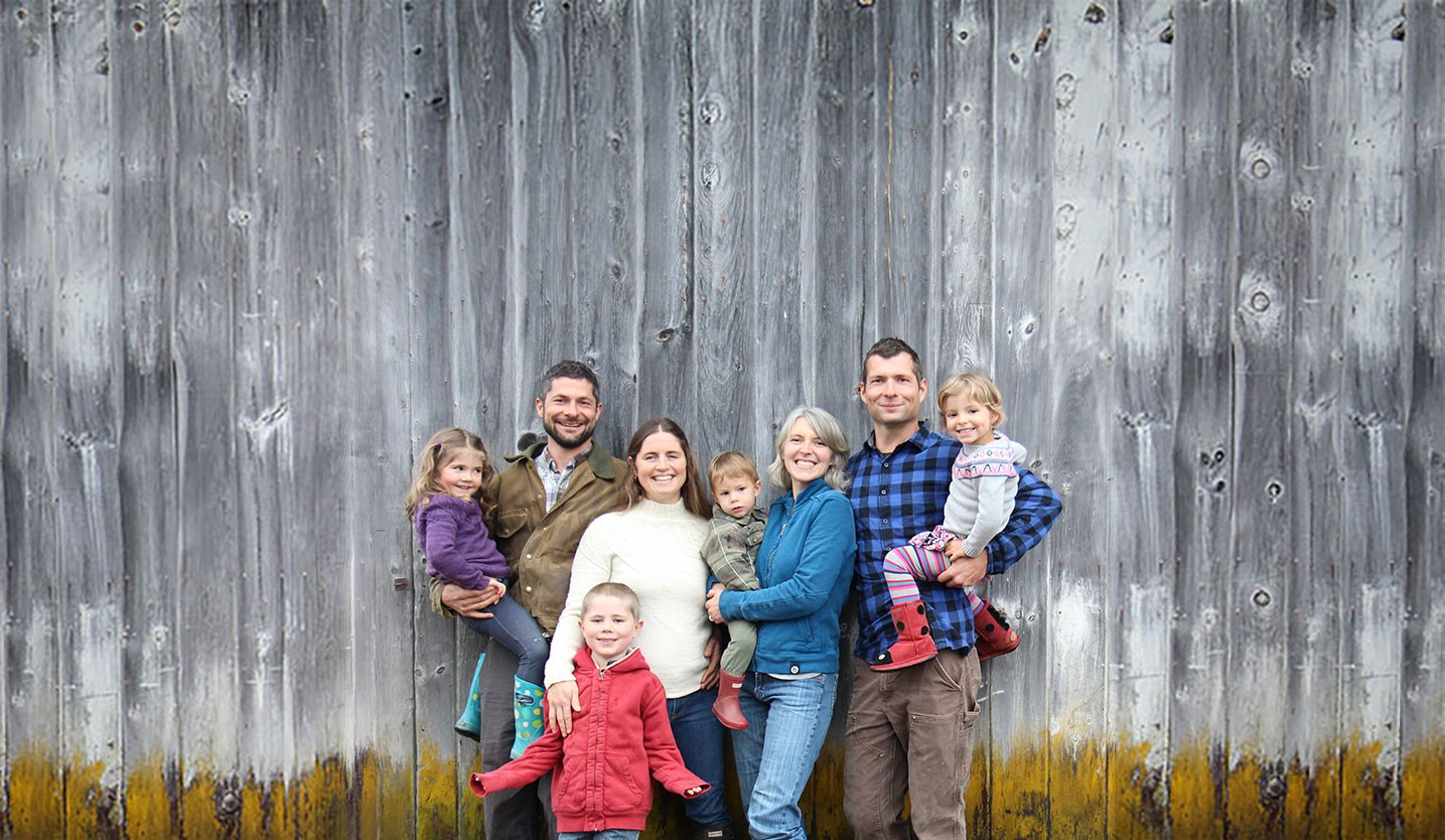 The owners of Cairncrest Farm in front of a barn.